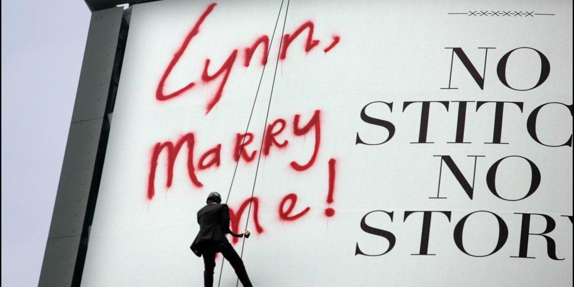 Trouwfotograaf Man schildert huwelijksaanzoek op reclamebord